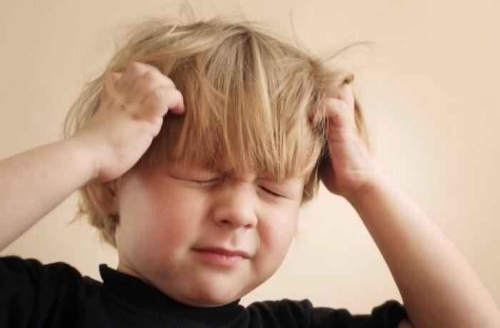 Bambino con i pidocchi si gratta la testa